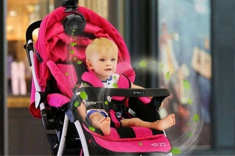 Clip-on fan attached to a baby stroller.
